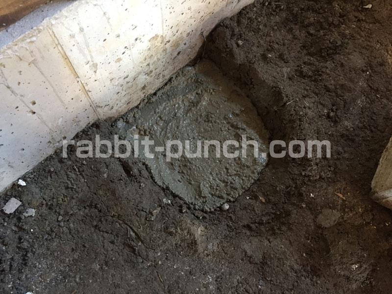 束石の穴にコンクリートを流し込む