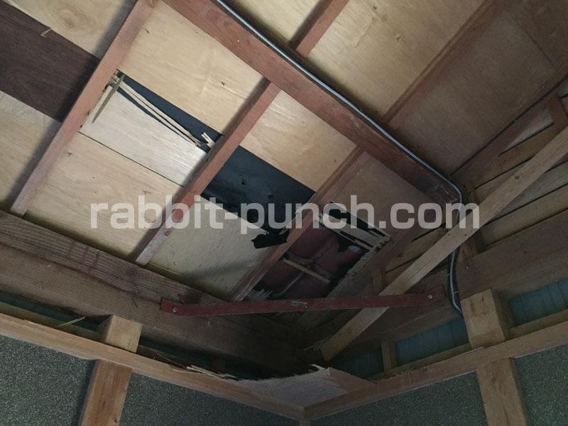 屋根下地のベニヤ板が剥がれて瓦が見えている