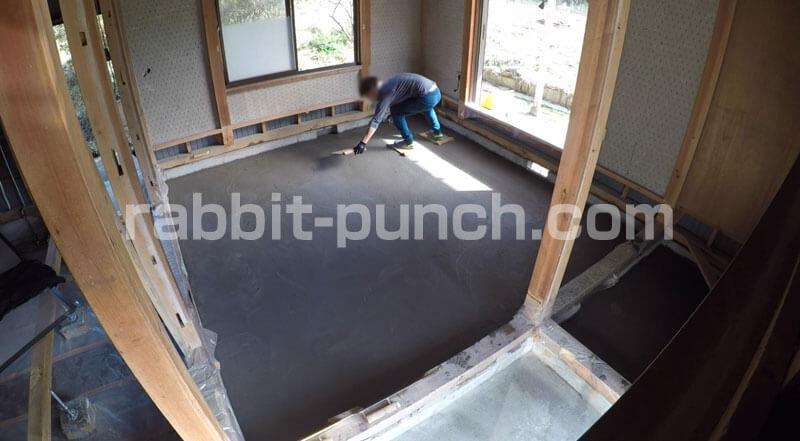 足場板に乗って土間コンクリートのコテ仕上げをする